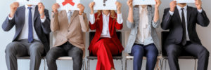 Young people holding paper sheets with different marks while sitting on chairs indoors. Job interview concept